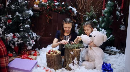 энтузиазм : Two little girls at a Christmas tree prepare a gift for the grandmother Стоковые видеозаписи