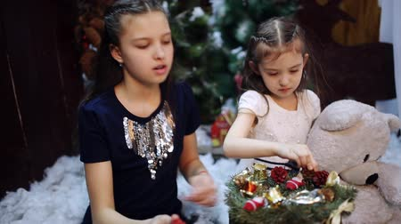 плюшевый мишка : Two little girls at a Christmas tree prepare a gift for the grandmother Стоковые видеозаписи