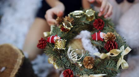 sisters : Two little girls at a Christmas tree prepare a Christmas wreath as a gift for the grandmother