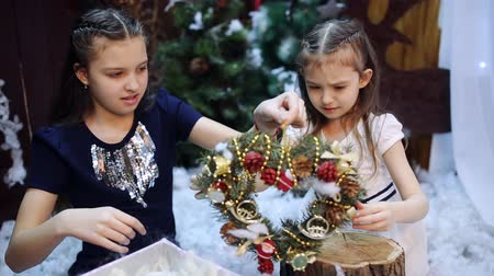adorno : Two little girls at a Christmas tree prepare a gift for the grandmother. Granddaughters pack a white shawl as a present to their beloved grandmother in a gift box.