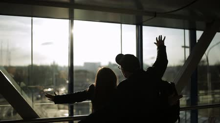 чемодан : Silhouette of tourists at the airport. Boy and girl are standing in front of a window and talking cheerfully. Woman slaps the guy shoulder and laughs.