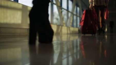 passar : Close-up of the feet of passengers pass through the corridor of the airport and wheeling suitcases.