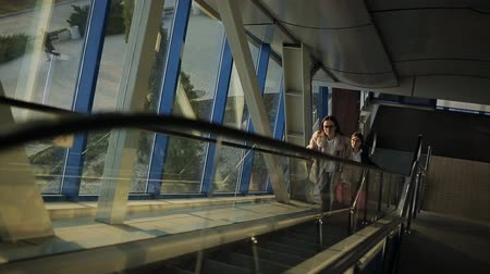 downwards : Two women passengers at the airport go up the escalator to the second floor.