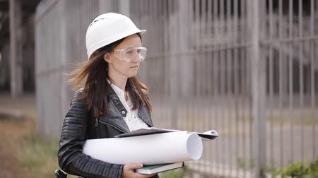 документация : Student girl in protective helmet and goggles and inspects the construction site, using the technical documentation Стоковые видеозаписи