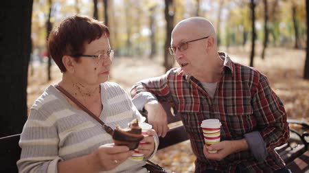 kruvasan : Elderly couple on a Park bench drinking coffee or tea from a Cup, eating croissants and nice talk. Stok Video