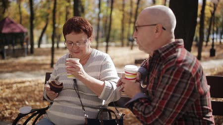 クロワッサン : Elderly couple on a Park bench drinking coffee or tea from a Cup, eating croissants and nice talk. 動画素材