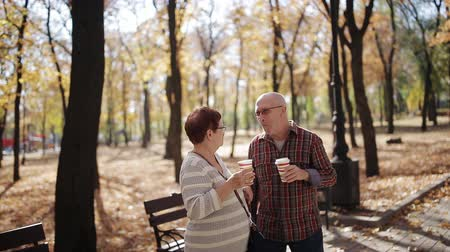 důchodce : An elderly married couple drinking coffee or tea from plastic cups in autumn Park. Dostupné videozáznamy
