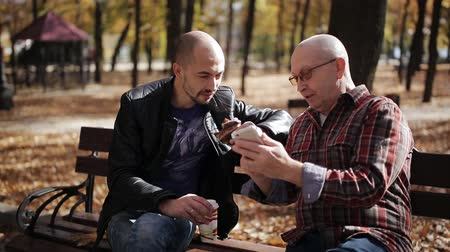 bank : Adult son of an elderly father teaches the smartphone in autumn Park on a bench. Stok Video