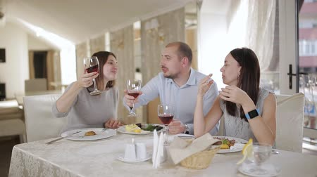 сороковые годы : Lunch break in restaurant in the company of best friends. A man and two women having lunch at restaurant and drinking wine.