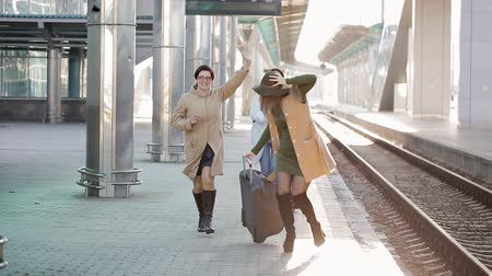 yakalandı : Women passengers running to catch the train before it leaves the railway station without them,
