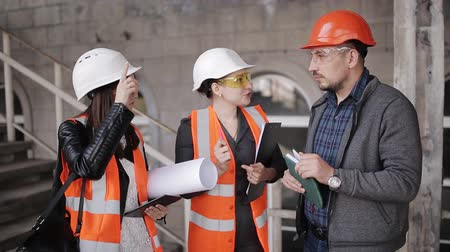 hard hat : The engineer communicates with the female customer representatives at the construction site, checking the drawings with the actual progress of construction work Stock Footage