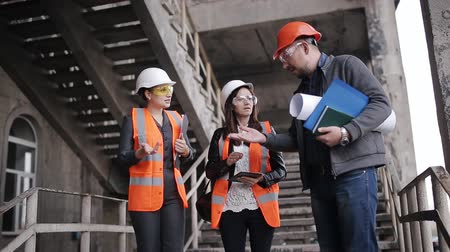 hard hat : The foreman and two women inspectors to discuss the plan of work performed on construction or restoration of the building.
