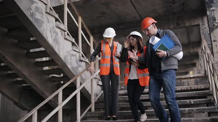pisos exteriores : Engineer and two women inspectors on-site construction or restoration site inspect stairwells and discuss the details of the construction or reconstruction. Archivo de Video