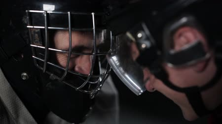 вратарь : The standoff between hockey players. Close-up of a goalkeeper and a forward face to face, forehead to forehead.