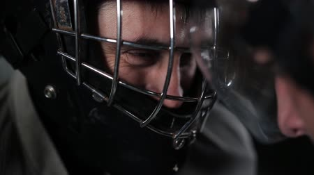 striker : Concept confrontation hockey players. Close-up of a goalkeeper and a forward head-on, helmet-to-helmet. The rage and hatred on the ice field. Stock Footage