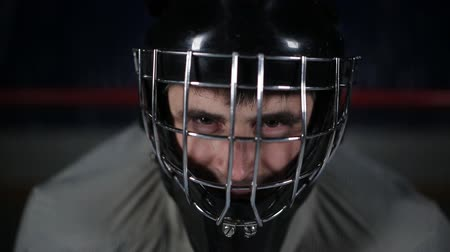 striker : Close-up goalie hockey player in protective helmet looking at the camera. The face of the goalkeeper in anticipation of the enemy. Stock Footage