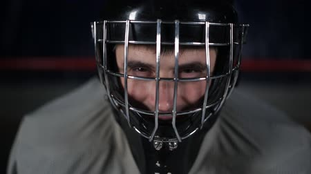 striker : Goalie hockey player waiting for the enemy stands at the gate. Close-up goalie helmet.