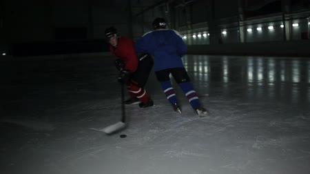 rakip : Two man playing hockey on ice rink. hockey Two hockey players fighting for puck. Stok Video
