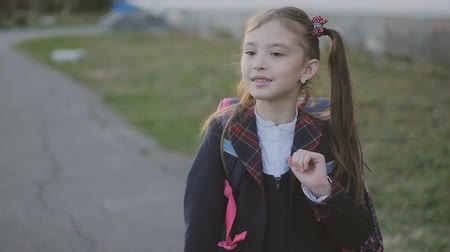 after school : Little schoolgirl sings a cheerful song and dances. Girl in school uniform and with a backpack. Slow motion