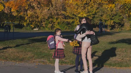 pozdrav : A happy mother meets her two daughters from school. Mom hugs and kisses her children in school uniform. Slow Motion in the Rays of the Sunset Dostupné videozáznamy