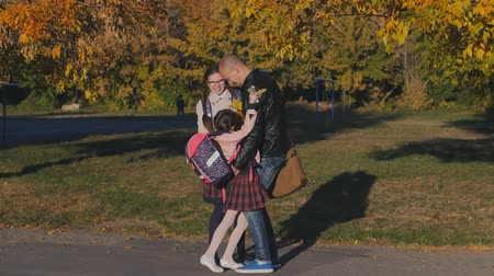 after school : Young happy father meets his daughters from school. Two girls in school uniform with dad. Slow Motion Autumn Sunset Stock Footage