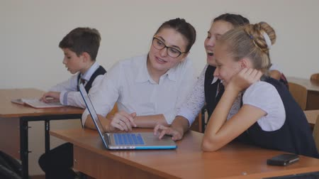 művelt : The teacher helps the students to do the task on the laptop. Lesson in computer class.