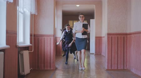 одноклассник : the girl teacher was almost knocked down by students running down the hall. Slow motion. The concept of school education