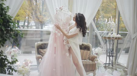negligee : The happy bride in a peignoir is spinning with her favorite pink wedding dress. Morning of the bride in the big light room with a gentle decor.