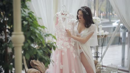 negligee : A happy bride in lingerie is admiring her wedding dress. Young girl in boudoir attire preparing to wedding