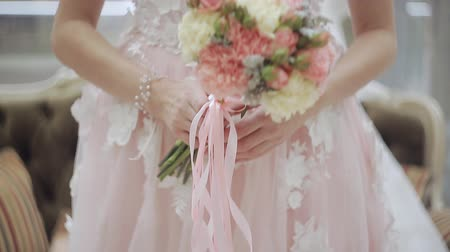 negligee : A young girl in a wedding dress picked up a wedding bouquet. Close-up Stock Footage