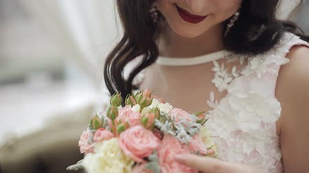 nevěsta : A young bride in a wedding dress is admiring a wedding bouquet. Close-up