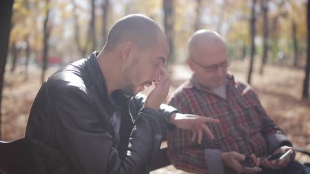 bank : Old father with adult son in Park on a bench, talk and drink coffee. Adult son of an elderly father teaches the smartphone in autumn Park on a bench.