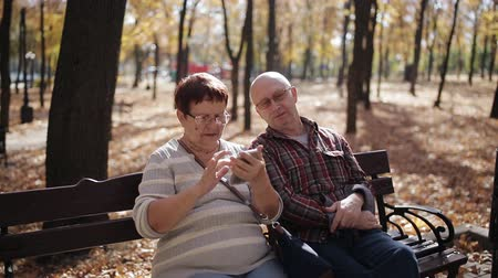 parentes : An elderly couple in the autumn Park-versed with the smartphone, browse photos and surf the Internet.