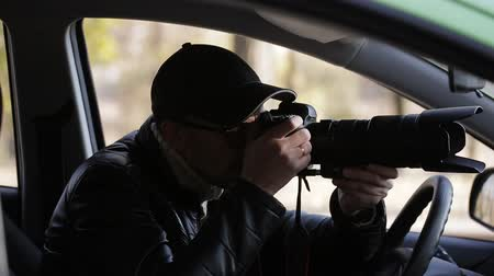 nesnel : Spy, paparazzi or detective in the car, shooting on camera.