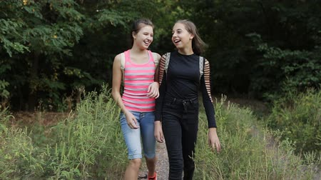 go to school : Two teenage girls are on the side of the road, talking and laughing