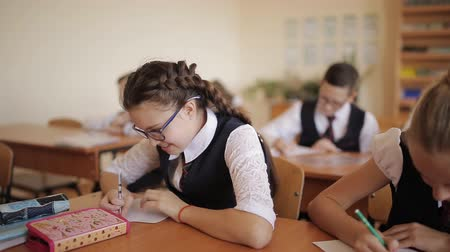 disciplina : Students in the class at their desks writing in notebooks for independent work.