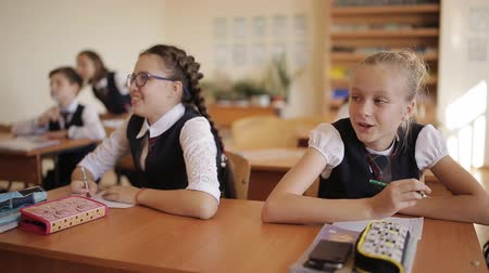 chłopcy : Students children sitting at their desks, some of them raise their hands