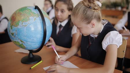 klasa : Schoolgirl in geography class studying the countries and continents with the globe.