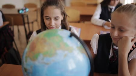 antwoord : Schoolgirl in geography class studying the countries and continents with the globe.