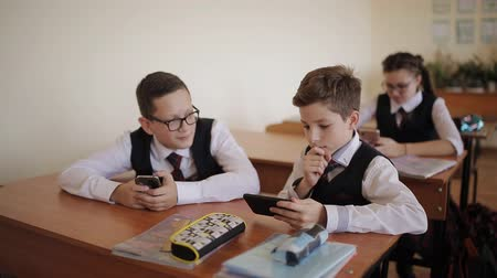 chłopcy : High school students play games on their phone during class.