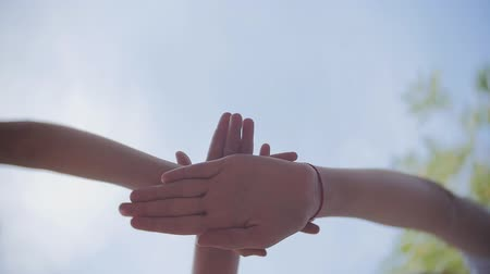 csatlakozott : Many hands together over sky and trees in slowmotion.