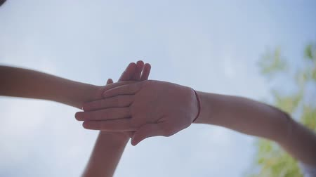 csatlakozott : Successful team: many hands holding together on sky background in slowmotion. Stock mozgókép