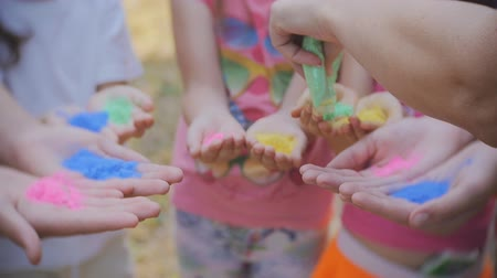 desejando : Palms of young people covered in purple, yellow, red, blue, pink. Holi festival colors Stock Footage