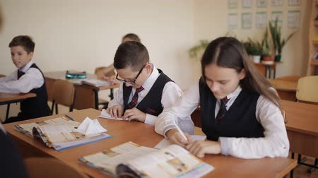tanítvány : The students in the classroom perform in notebooks the instructions of the teacher, and one of the students makes a paper airplane.