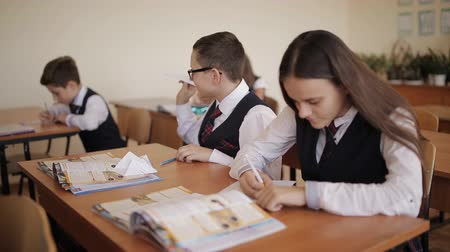 tanítvány : Naughty student in the class starts a paper airplane, while the other students diligently writing in their notebooks. Stock mozgókép