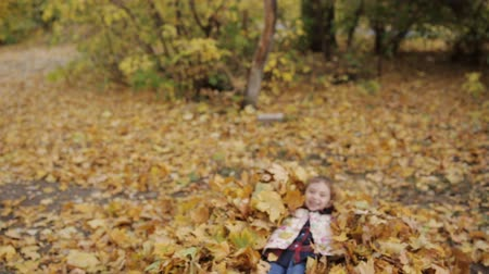 ancinho : A little girl plays with yellow leaves and falls into them. Vídeos