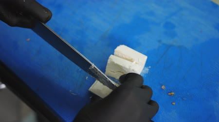 пармезан : chef in the kitchen. A hand in gloves cuts cheese into cubes