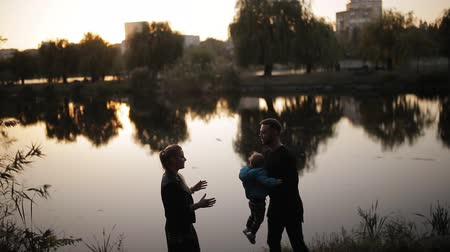 Happy family in autumn Park against the background of the lake, the silhouettes.