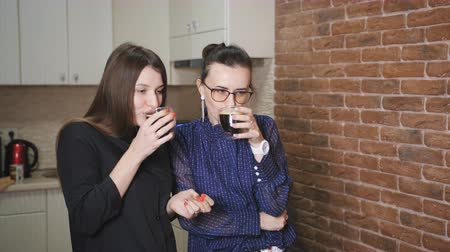 pauza : Two business women in the kitchen, in the office drinking coffee and talking during the break.