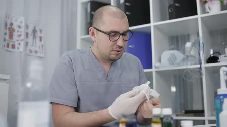 pipette : A doctor in glasses sitting at the table puts on rubber gloves. Pharmacology and medicine concept